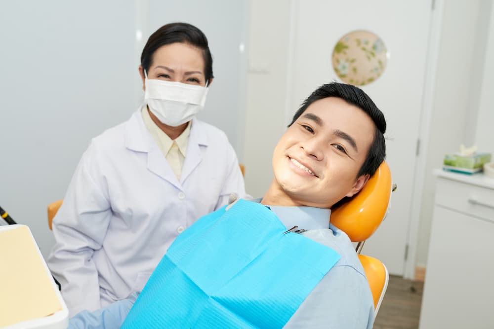 smiling-ethnic-dentist-and-man-in-dental-chair-CNVS7GE (1)